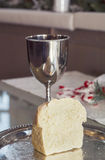 Tasse et pain de communion Photographie stock