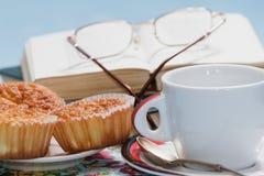 Tasse et petits pains devant le livre avec des verres Photographie stock