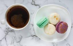 Tasse et plat de café avec des macarons sur le fond de marbre de table Pause-café délicieuse photos stock