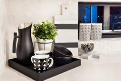 Tasse et plats modernes près de vase et de cruche à fleur Photographie stock libre de droits