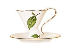 Tasse et soucoupe antique de thé de la Chine avec des feuilles. photos libres de droits
