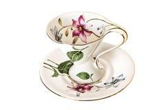 Tasse et soucoupe antique de thé de la Chine avec des feuilles et des fleurs sensibles images stock