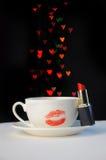 Tasse et soucoupe blanche avec l'empreinte rouge de rouge à lèvres d'un baiser et de lui Images stock