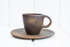 Tasse et soucoupe d'argile de tasse et soucoupe d'argile sur un fond en bois blanc Photos stock