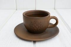 Tasse et soucoupe d'argile de tasse et soucoupe d'argile sur un fond en bois blanc Image stock