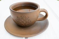 Tasse et soucoupe d'argile de tasse et soucoupe d'argile sur un fond en bois blanc Photo stock