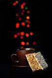 Tasse et soucoupe de Brown avec des biscuits sur un fond noir Image libre de droits