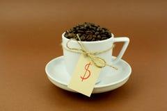 Tasse et soucoupe de café avec les grains de café et le symbole dollar d'arc Photographie stock libre de droits
