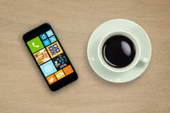 Tasse et téléphone portable de café sur la table en bois Photos libres de droits