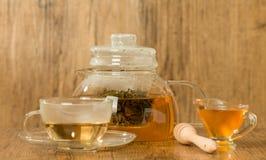Tasse et théière en verre avec le thé vert avec du miel Photo stock
