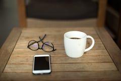 Tasse et verres de café avec le téléphone portable sur la table en bois Photographie stock