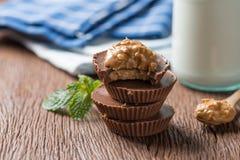 Tasse faite maison de beurre d'arachide, pile de chocolat foncé avec la bouteille à lait, nourriture de dessert images stock