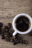 Tasse, grains de café sur le fond de vue supérieure de plan rapproché de conseil en bois Photos stock