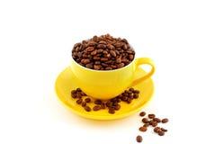 Tasse jaune avec la soucoupe pleine des grains de café Images libres de droits