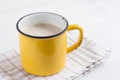 Tasse jaune de café de cappuccino sur un fond dans le ton Photos libres de droits