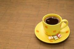 Tasse jaune de café et de sucreries sur la couverture en bois Image libre de droits