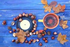 Tasse jaune de tisane sur le fond en bois âgé avec des feuilles et des châtaignes d'automne de chute Photographie stock