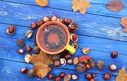 Tasse jaune de tisane sur le fond en bois âgé avec des feuilles et des châtaignes d'automne de chute Images libres de droits