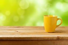 Tasse jaune sur la table en bois au-dessus du fond vert de bokeh photos stock