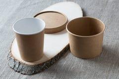 Tasse jetable de papier d'emballage sur un conseil en bois photos stock
