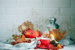 Tasse Kaffee, Äpfel und Herbstlaub auf einem Holztisch Rot und Orange färbt Efeublattnahaufnahme stockfoto