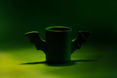 Tasse Kaffee als Schläger für Halloween auf schwarzem Hintergrund Grünes Licht und Schatten spielzeug Konzept Stockfoto