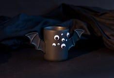 Tasse Kaffee als Schläger für Halloween mit Augen auf schwarzem Hintergrund Grünes Licht und Schatten spielzeug Konzept Stockfotografie