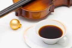 Tasse Kaffee, alte Violine und Weihnachtsdekoration auf dem Weiß Stockfotografie