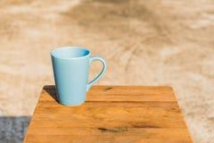 Tasse Kaffee auf altem hölzernem Brett Blauer Becher hölzern Stockfotografie