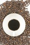 Tasse Kaffee auf Bohnen Stockbilder