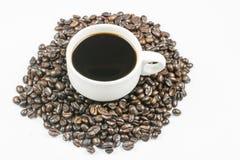 Tasse Kaffee auf Bohnen Stockbild