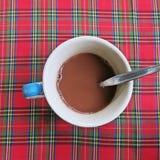 Tasse Kaffee auf buntem Tischdeckenhintergrund des gestreiften Musters Stockfotos
