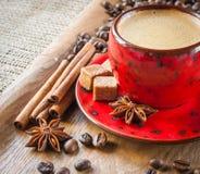 Tasse Kaffee auf dem hölzernen Hintergrund verziert mit Gewürzen Stockbild