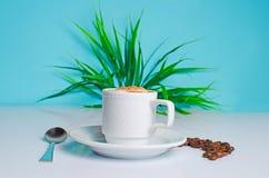 Tasse Kaffee auf dem Tisch mit Bohnen auf einem blauen Hintergrund lizenzfreie stockfotos