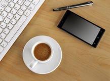 Tasse Kaffee auf dem Tisch mit Tastatur Stockfotos