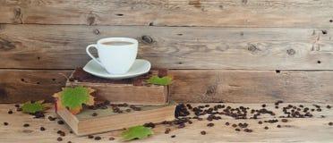 Tasse Kaffee auf den Büchern in den Herbstahornblättern Stockbilder