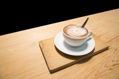 Tasse Kaffee auf der hölzernen Tabelle lokalisiert auf schwarzem Hintergrund Lizenzfreie Stockfotografie