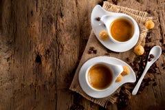Tasse Kaffee auf dunklem hölzernem Hintergrund mit kleinen Bonbons stockfotografie
