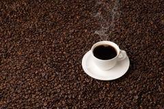 Tasse Kaffee auf einem Bett von Bohnen Stockfoto