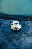 Tasse Kaffee auf einem gefrorenen blauen Auto Stockfoto