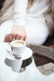 Tasse Kaffee auf einem Glastisch mit einem Mädchen in einer weißen Klage wieder Lizenzfreies Stockfoto