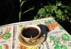 Tasse Kaffee auf einem Hintergrund der Vegetation Stockfotos