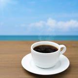 Tasse Kaffee auf einer hölzernen Tabelle auf einem Hintergrund des blauen Himmels Lizenzfreies Stockbild