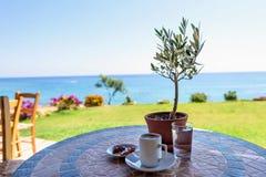 Tasse Kaffee auf einer Tabelle mit Olivenbaum Stockfotos