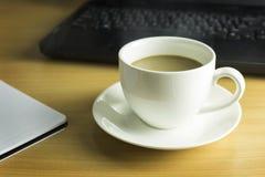 Tasse Kaffee auf hölzernem Schreibtisch Lizenzfreie Stockfotografie