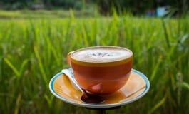 Tasse Kaffee auf hölzerner Terrasse mit grünem Reisfeld Stockbild
