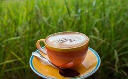 Tasse Kaffee auf hölzerner Terrasse mit grünem Reisfeld Stockbilder