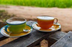 Tasse Kaffee auf hölzerner Terrasse mit grünem Reisfeld Lizenzfreie Stockfotografie