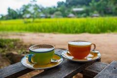 Tasse Kaffee auf hölzerner Terrasse mit grünem Reisfeld Stockfotografie