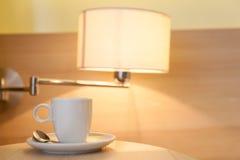 Tasse Kaffee auf Holztisch im Hotel Lizenzfreie Stockfotografie